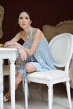 Mulher bonita que senta-se em uma cadeira no interior refinado imagem de stock royalty free