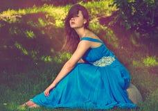 Mulher bonita que senta-se em uma pedra fotos de stock royalty free