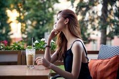 Mulher bonita que senta-se em uma tabela em um café no terraço no verão, latte, café foto de stock royalty free