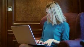 Mulher bonita que senta-se na cadeira luxuosa e que datilografa no teclado do caderno fotos de stock