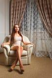 Mulher bonita que senta-se na sala de estar do couro branco imagem de stock royalty free