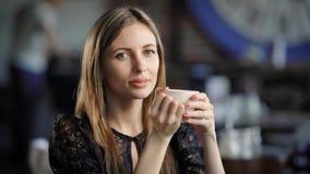 Mulher bonita que senta-se na tabela no restaurante com fundo borrado e que guarda a xícara de café Senhora adorável vídeos de arquivo