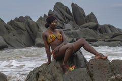 Mulher bonita que senta-se nas pedras da praia de Axim imagens de stock royalty free