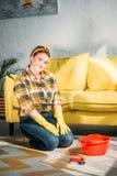 mulher bonita que senta-se no assoalho com fontes para o tapete de limpeza imagem de stock