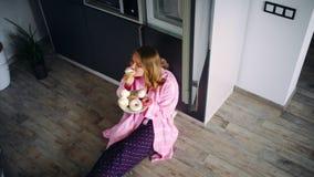 Mulher bonita que senta-se no assoalho na cozinha e que come doces Menina satisfeita vídeos de arquivo