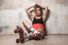 Mulher bonita que senta-se no assoalho na patinagem de rolo imagens de stock