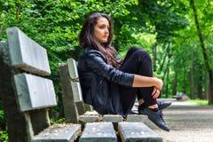 Mulher bonita que senta-se no banco Imagem de Stock