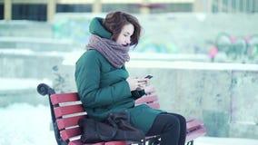 Mulher bonita que senta-se no banco no parque e que usa a paisagem esperta do inverno do telefone Menina bonita que datilografa u filme