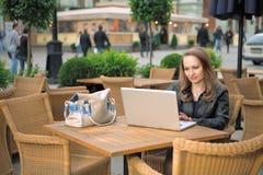 Mulher bonita que senta-se no café da rua com portátil Imagem de Stock