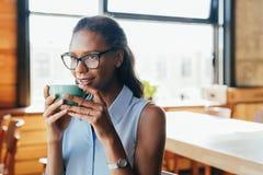 Mulher bonita que senta-se no caf? foto de stock royalty free