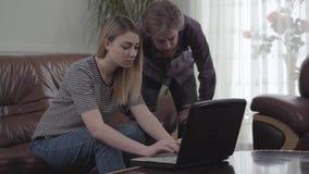 Mulher bonita que senta-se no sofá de couro e na posição farpada do homem perto de seu funcionamento com portátil A menina vem co vídeos de arquivo