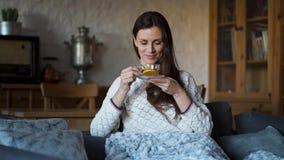 A mulher bonita que senta-se no sofá envolveu em uma cobertura e em um chá bebendo video estoque
