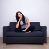 Mulher bonita que senta-se no sofá e que pensa sobre algo Imagens de Stock Royalty Free