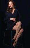 Mulher bonita que senta uma cadeira, isolada no fundo preto Imagens de Stock