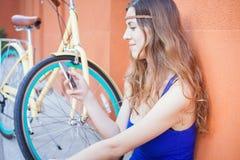 A mulher bonita que sentam-se perto da parede e o vintage bicycle Imagem de Stock Royalty Free