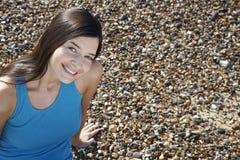 Mulher bonita que sorri ao sentar-se na praia imagem de stock royalty free