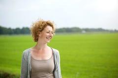 Mulher bonita que sorri fora pelo campo verde Fotos de Stock Royalty Free