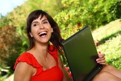 Mulher bonita que sorri guardando um computador que aprecia o dia ensolarado Imagem de Stock
