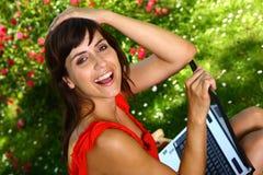 Mulher bonita que sorri guardando um portátil Imagem de Stock