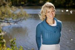 Mulher bonita que sorri no lago fotografia de stock