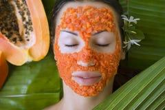 A mulher bonita que tem a máscara facial da papaia fresca aplica-se pap fresco foto de stock