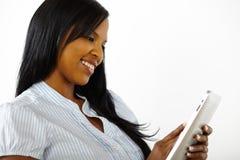 Mulher bonita que tem o divertimento com um PC da tabuleta Fotografia de Stock Royalty Free