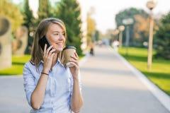 Mulher bonita que texting em um telefone esperto em um parque com um verde Imagem de Stock Royalty Free