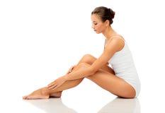 Mulher bonita que toca em seus pés desencapados lisos imagem de stock royalty free