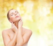 Mulher bonita que toca em sua cara com olhos fechados Fotos de Stock Royalty Free