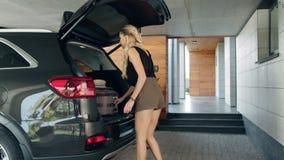 Mulher bonita que toma a bagagem do carro na casa rica Turista fêmea que vem em casa vídeos de arquivo