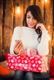 A mulher bonita que toma a foto do selfie no telefone celular próximo decorou a parede do Natal com ampolas imagem de stock