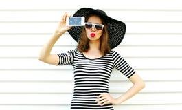 Mulher bonita que toma a imagem do selfie pelo telefone que funde os bordos vermelhos que enviam o beijo doce do ar no fundo bran imagem de stock