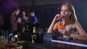 Mulher bonita que toma o cocktail do empregado de bar no clube video estoque
