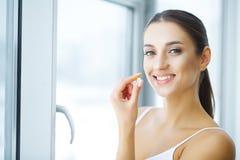 Mulher bonita que toma o comprimido, medicina Vitaminas e suplementos fotografia de stock royalty free