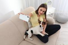 Mulher bonita que toma o selfie com seu cão no sofá fotos de stock