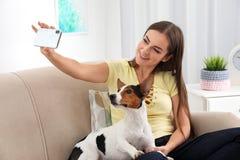 Mulher bonita que toma o selfie com seu cão no sofá fotografia de stock royalty free