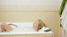 Mulher bonita que toma um banho e que escuta a música em fones de ouvido Teclas do telefone da pilha Phone vídeos de arquivo