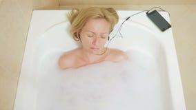 Mulher bonita que toma um banho e que escuta a música em fones de ouvido Teclas do telefone da pilha Phone filme