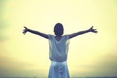 Mulher bonita que toma uma respiração profunda no por do sol Imagem de Stock