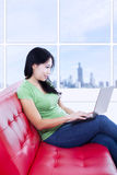 Mulher bonita que trabalha com o portátil no sofá vermelho Foto de Stock