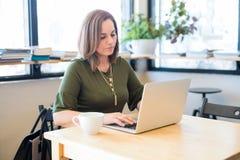 Mulher bonita que trabalha no portátil em um café fotografia de stock royalty free