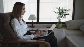 A mulher bonita que trabalha no portátil Perto de Windows grande e de uma flor em um potenciômetro filme
