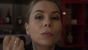 A mulher bonita que usa a escova cosmética para cora e pulveriza para compõe a cara video estoque