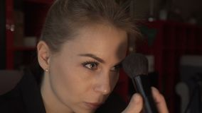 A mulher bonita que usa a escova cosmética para cora e pulveriza compõe dentro a cara video estoque