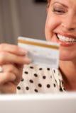 Mulher bonita que usa o cartão de crédito da terra arrendada do portátil Foto de Stock