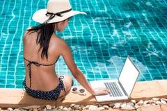 Mulher bonita que usa o laptop em férias no reso luxuoso foto de stock royalty free