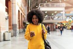 Mulher bonita que usa o móbil no estação de caminhos-de-ferro foto de stock