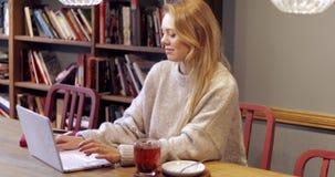 Mulher bonita que usa o portátil na biblioteca video estoque