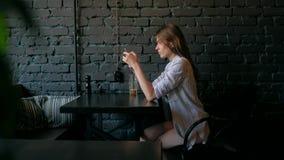 Mulher bonita que usa o smartphone e bebendo o café no café video estoque