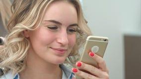 Mulher bonita que usa o smartphone em um salão de beleza, ao ter uma denominação do cabelo Imagem de Stock